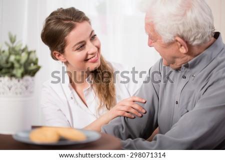Young volunteer visiting elder man in need - stock photo