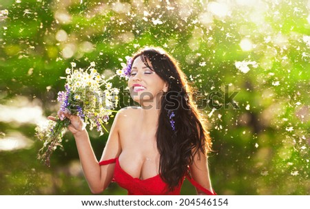 Young voluptuous brunette holding  a wild flowers bouquet in a sunny day. Portrait of beautiful woman with low-cut red dress laughing, outdoor shot. Provocative female enjoying the nature - stock photo