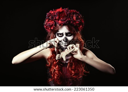 Young voodoo witch with muertos makeup (sugar skull) piercing a doll - stock photo