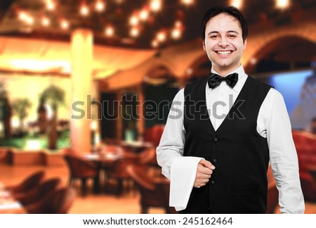 Young waiter at the restaurant - stock photo