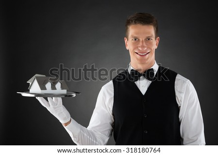 Young Waiter Holding Tray With Small House Model - stock photo