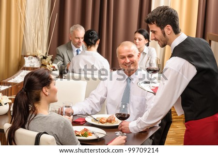 Young waiter serve wine to business people at professional restaurant - stock photo