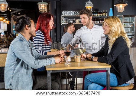 Young waiter serving wine to customers at table in bar - stock photo