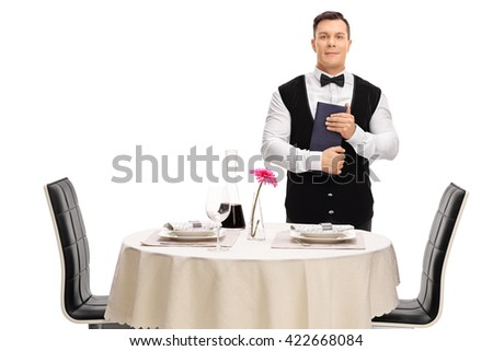 Young waiter standing next to a restaurant table and holding a menu isolated on white background - stock photo