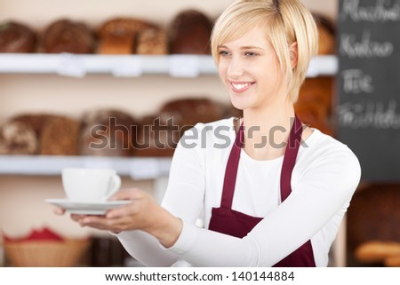 Young waitress giving coffee cup in cafe - stock photo