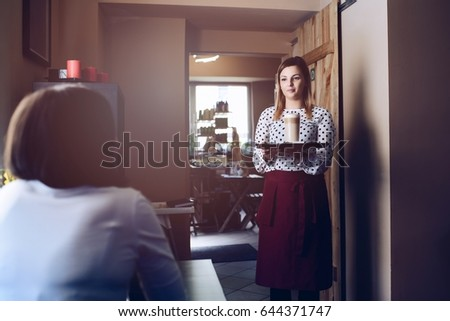 Young waitress in apron serving coffee latte at the cafe