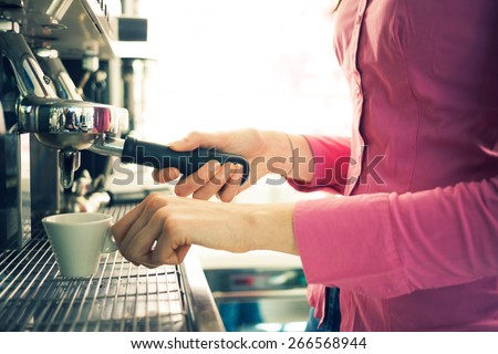 Young waitress making coffee with an espresso coffee machine, she is holding a cup and the filter holder - stock photo
