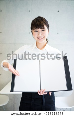 young waitress showing menu in a cafe - stock photo