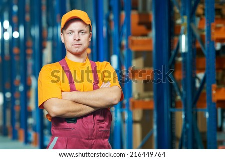young warehouse worker portrait in uniform in front of modern storehouse shelves - stock photo