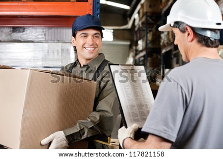 Young warehouse worker with cardboard box looking at male supervisor with clipboard - stock photo