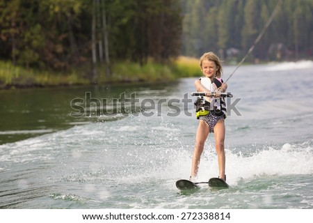 Young Waterskier water skiing on a beautiful scenic lake  - stock photo