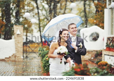 Young wedding couple and first snow in november.  - stock photo