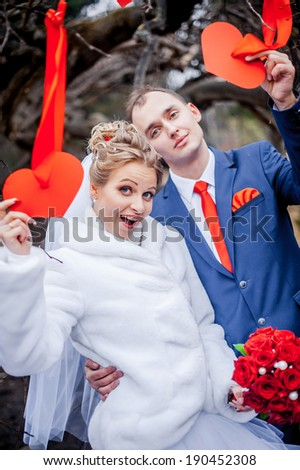 young wedding couple, beautiful bride with groom portrait on outdoor. tree decorated with red hearts. Funny couple - stock photo