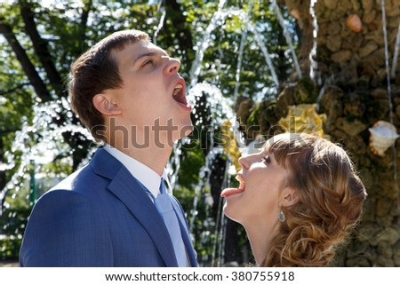Young wedding couple drinking water from fountain in park - stock photo