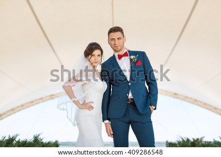 Young wedding couple enjoying romantic moments looking at cameraoutside against modern buildings - stock photo