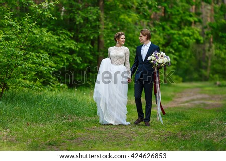 Young wedding couple holding hands and walking together at park.