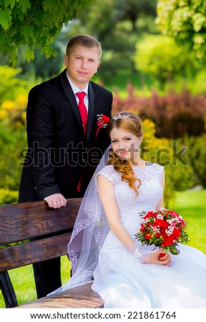 Young wedding couple in a park on the wedding day - stock photo