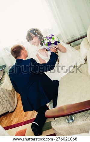 Young wedding couple indoors portrait. Charming bride and groom on their wedding celebration in a luxurious restaurant. - stock photo