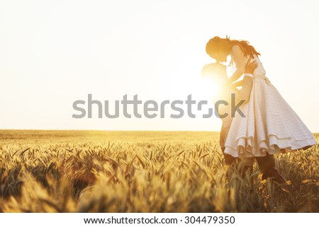 Young wedding couple kissing in the field on sunset - stock photo