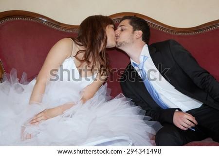 Young wedding couple on a vintage sofa - stock photo
