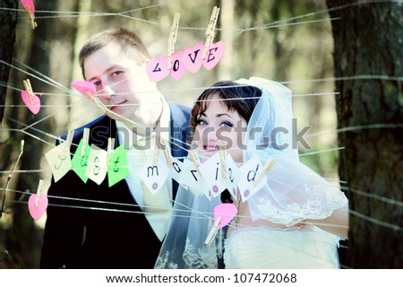 Young wedding couple outdoors funny portrait - stock photo