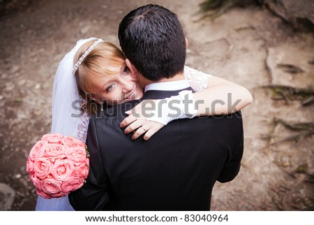 young wedding couple outdoors on their wedding day - stock photo