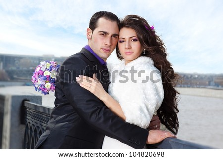 Young wedding couple portrait on river background.