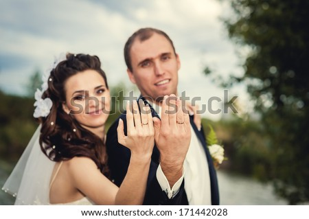 Young wedding couple showing their rings. Focus on hands.