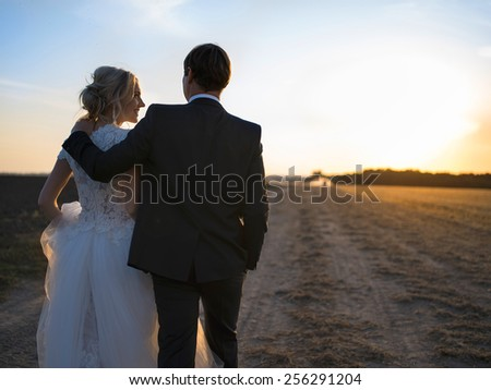 Young wedding couple talking in an embrace on the field at sunset. Newlyweds back to Kemer look at each other. - stock photo