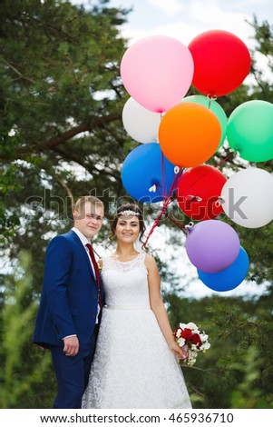 Young wedding couple with colored balloons hugging in the pine forest