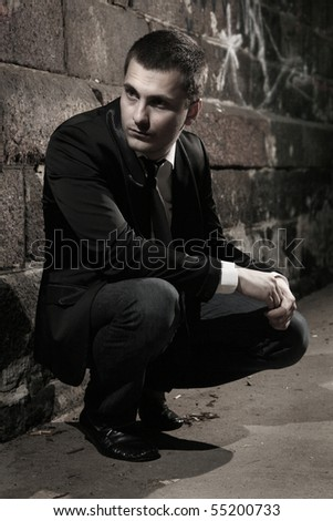 young well-dressed guy sitting in the dark - stock photo
