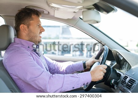Young well-dressed man is driving his car with passion. He is looking forward with aggression