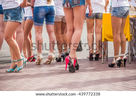 Young well-fitted women in shorts preparing to race on heels. Slim legs in heel shoes.