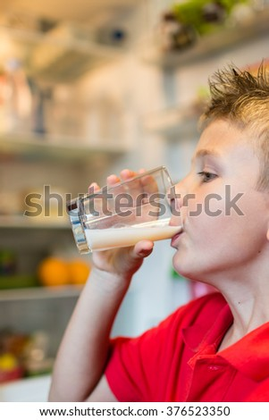 Young white boy drinking fresh milk from a glass while standing in front of open refrigerator.