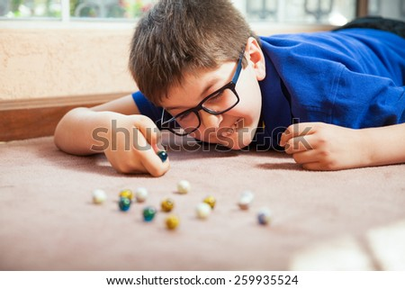 Young white boy playing with marbles and aiming at one at home - stock photo