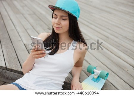 Young white brunette girl using her modern smart phone with dual camera while sitting in the park outdoors with her skateboard. Attractive model, new technology - stock photo