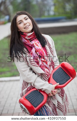 Young white brunette woman holding modern red electric mini hover board scooter in hands. Popular new electric city transport. Girl is wearing trending boho style clothes. - stock photo