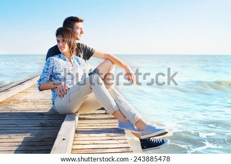 Young White Couple Relaxing on Wooden Pier While Viewing the Beautiful Sea on Tropical Climate. - stock photo