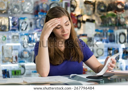Young white female entrepreneur running a small business and working in computer shop, checking bills and invoices with worried expression - stock photo