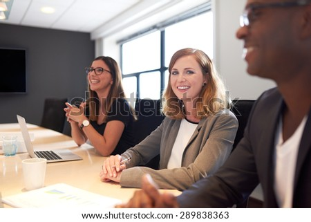 Young white female executive smiling at camera with hands clasped during meeting in conference room