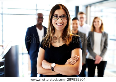 Young white female executive standing in front of colleagues with arms crossed and smiling - stock photo