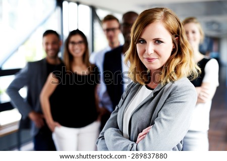 Young white female executive with arms crossed standing in front of colleagues grinning at camera - stock photo