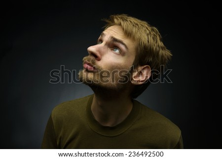 Young white man looking upward into a light over a dark background - stock photo