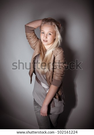 Young white skin girl posing in studio holding hand up