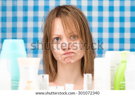 Young white-skinned girl with wet hair without makeup is in disbelief in front of cosmetic products. Skincare and beauty concept. Frontal portrait - stock photo