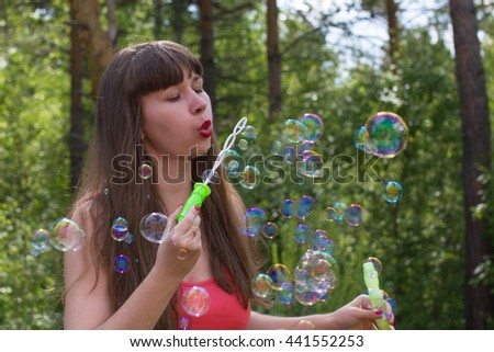 Young white woman make bubble blower outdoors