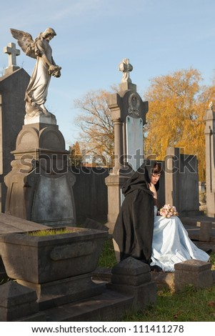 Young widow in Victorian dress sitting on a tombstone - stock photo