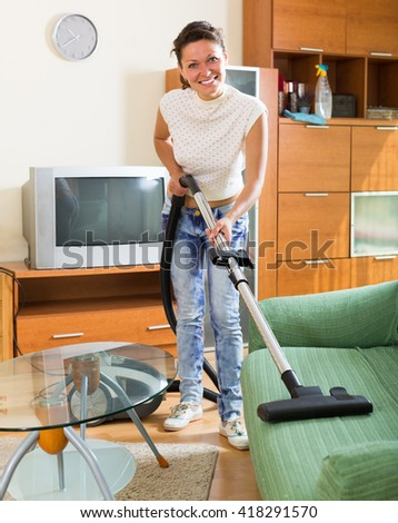 Young wife with vacuum cleaner at living room