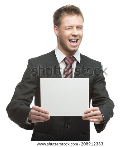 young winking caucasian businessman in black suit holding sign isolated on white