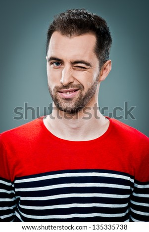 Young Winking Man Over a Grey Background - stock photo
